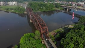 Slow Reverse Aerial View of Small Town USA and Rail Road Bridge. ROCHESTER, PA - Circa May, 2018 - A slow reverse morning aerial establishing shot view of a stock video footage