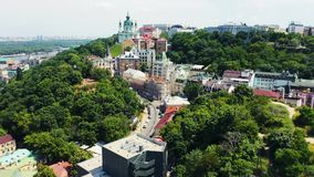 Slow rising shot over bushy hill revealing Andrew`s descent and Andrews Church in Kiev. Famous place in Kyiv. Aerial. Footage 4k stock footage