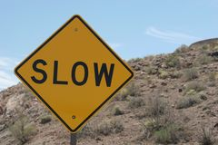 Slow road sign. Slow ahead traffic sign on blue sky Royalty Free Stock Photography