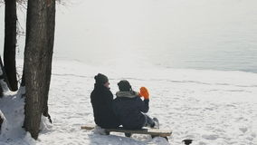 Slow shooting from back couple in winter on bank of lake outdoors. Loving pair sit on bench among snow in romantic atmosphere. Attractive female in blue warm stock video footage