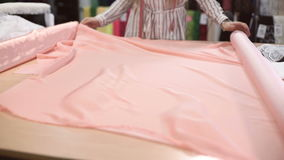 Slow shooting fabric store worker unwraps pink roll atlas tissue. On table. Blonde married woman with long wavy hair, striped shirt takes edge of light smooth stock footage