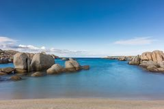 Rocky coastline and sandy beach at Cavallo island near Corsica. Slow shutter image of deserted sandy beach and boulders on coast of Cavallo island near Corsica Stock Images