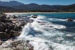 Waves crashing onto rocks near Algajola beach in Corsica. Slow shutter image of waves crashing onto rocks near Algajola beach in the Balagne region of Corsica royalty free stock image