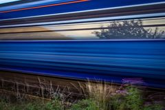 Slow shutter shot of blue and red train speeding past stock photo