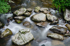 Slow Shutter Speed of Creek Through Rocks. Water cascading over rocks in a creek is captured with a long exposure stock photo