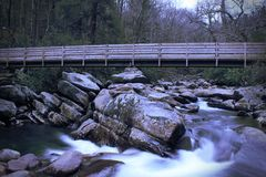 Slow Shutter Speed Motion Photography of a Wooden Bridge over a Rushing Waterfall. Slow Shutter Speed Photography of a Wooden Bridge over a Rushing Waterfall Stock Image