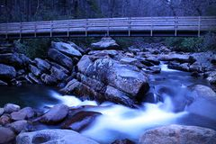 Slow Shutter Speed River Photography of a Small Waterfall with a Wooden Walk Way Bridge over the River. stock photo