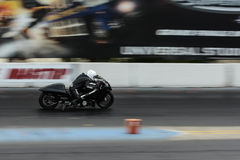 Slow shutter speed shot of a motorcycle accelerating down a race Royalty Free Stock Photos