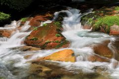 Slow shutter speed water fall on rock. Waterfall on colorful rock stock images