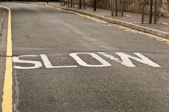 Slow sign on a bend in Edinburgh road, UK Stock Image