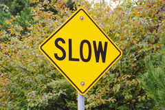 Slow Sign. A bright yellow sign alerts motorists to slow down stock images