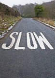Slow sign on a country lane. Slow sign painted on a country lane before a corner Stock Photo