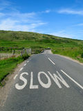 Slow sign on an English road. Royalty Free Stock Photo