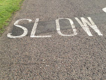 Slow sign on the street. Slow sign on the pavement of a street in England stock photos