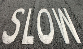 Slow sign on the road. A white slow sign on the road Royalty Free Stock Photography