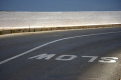 Slow sign on the road. A white slow sign on the road stock photo