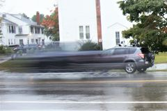 Slow speed photograph of small green SUV rushing to leave. On rain slicked road in early all in Groton. Massachusetts, middlesex county stock photo