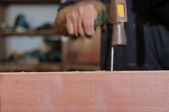 Slow speed sync of nail is hit against hammer on hand of carpenter. Royalty Free Stock Photos
