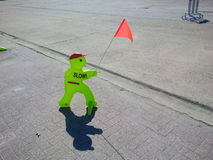 Slow!. Standing figure of a child with a red flag that has to remind motorists to slow down Royalty Free Stock Photos