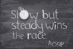 Slow but steady Aesop. Slow but steady wins the race - quote of ancient Greek story teller Aesop written on chalkboard with stopwatch instead of O stock photos