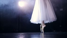 Slow steps on dancing pointe shoes under a spotlight. An electrical lamp spotting ballerinas legs as she steps on her pointe shoes stock footage
