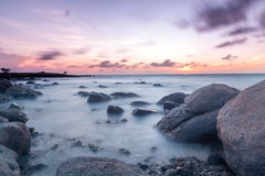 Slow Sunset. A long exposure of a sunset on aruba near west point. The rocky coast provides nice rocks in the water. Long exposure makes the caribbean sea look Stock Photo