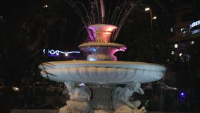 Slow tilt of illuminated fountain at the night. Wide shot stock footage