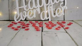 Slow tilt shot of Happily ever after sign with red hearts around and lights, red baloon on background. Valentines day. Slow tilt shot of Happily ever after sign stock video footage