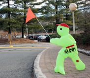 Slow Traffic Sign. Green Figure with a slow sign holding an orange flag. warning drivers to slow down royalty free stock photography