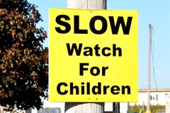 Slow watch for children sign. Posted on the wooden pole Stock Image