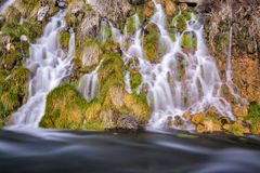 Slow water of a spring glides over rocks Royalty Free Stock Photos