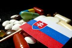Slowaakse vlag met partij van medische die pillen op zwarte backg wordt geïsoleerd Royalty-vrije Stock Afbeeldingen