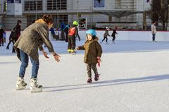 Slowakije, het ijs van December 2018 het schaatsen Mamma en kindvleet op het schaatsen schoenen Gelukkig familie openluchtijs die stock fotografie