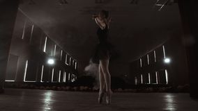 A slowly dancing ballerina in front of spot lights. Several spotlights show a dancing ballerina at a dark stage in slow. Motion stock footage