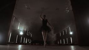A slowly dancing ballerina in front of spot lights. Several spotlights show a dancing ballerina at a dark stage in slow. Motion stock video footage