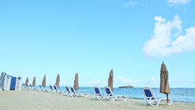Slowly panorama at empty sandy seashore with beach chairs and closed umbrellas