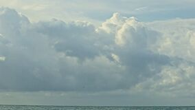 Slowly panorama left on large fluffy grey clouds float above calm blue ocean