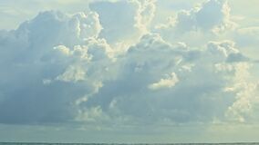Slowly panorama right on large fluffy white clouds float above endless blue sea