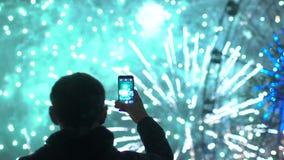 Slowmotion силуэта крупного плана человека наблюдать и фотографировать фейерверки взрывают на камере smartphone outdoors