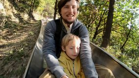 Slowmotion съемка катания отца и сына вниз с высокогорных русских горок в лесе осени видеоматериал