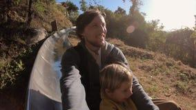 Slowmotion съемка катания отца и сына вниз с высокогорных русских горок в лесе осени акции видеоматериалы