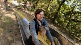 Slowmotion съемка катания отца и сына вниз с высокогорных русских горок в лесе осени сток-видео