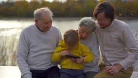 Slowmotion съемка grandgrandson вместе с его отцом учит его родителям grandgrand как использовать применения на его акции видеоматериалы