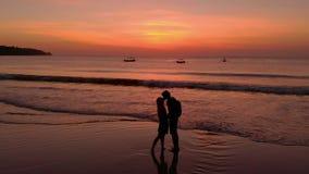 Slowmotion antennskott av ett ungt par som kysser under solnedgång med deras köra för son som är närliggande lager videofilmer