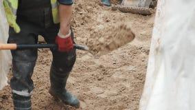Slowmotion Arbeitskraft in den Gummistiefeln mit der Schaufel, die Sand im Graben glatt macht stock video