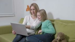 Slowmotion - Attractive young family or mother and daughter using a laptop to make future plans.  stock footage
