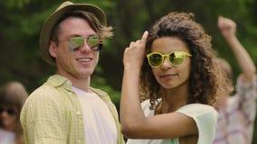 Slowmotion av barn koppla ihop i solglasögon som ler till kameran, lyckligt krama för folk lager videofilmer