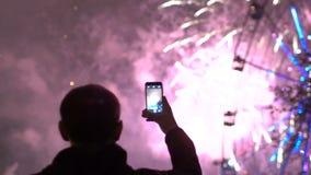 Slowmotion av closeupkontur av mannen exploderar att hålla ögonen på och att fotografera fyrverkerier på smartphonekamera utomhus lager videofilmer