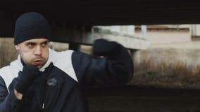 Slowmotion av den sportive manboxaren som utomhus gör boxningövning i stads- läge i vinter stock video