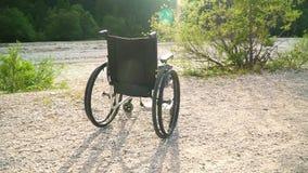 Slowmotion av den tomma rullstolen utanför i solig sommar parkera med ljust solsken på bakgrundsgräsplannaturen som lyfter solen lager videofilmer